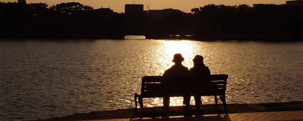 川辺のベンチに座るシニア世代の夫婦
