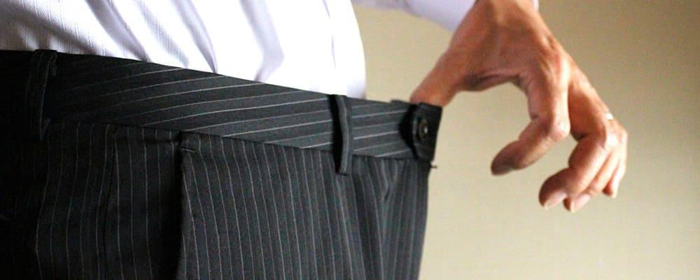 サイズ違いのスーツを着る男性