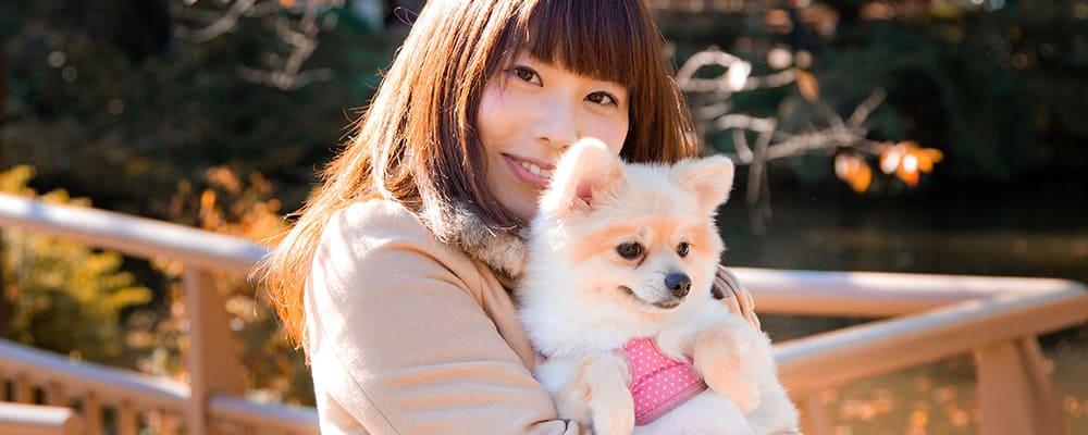 愛犬と一緒に写真にポーズする女性