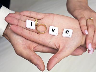 重なる手のひらに置かれた指輪と文字