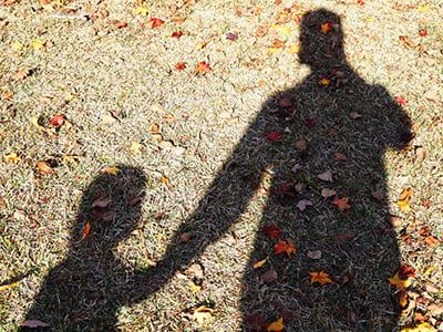 手をつないだ親子の影