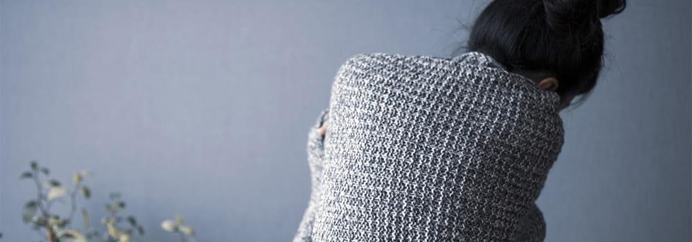毛布にくるまり寂しがる女性