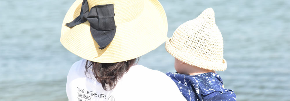 海を見る母親と幼い子供