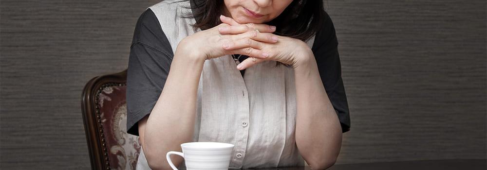 コーヒーを飲み肘をつく熟年女性