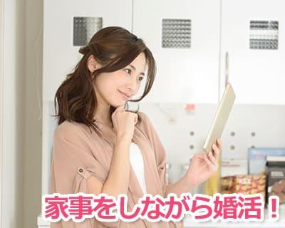 キッチンに立ちながら婚活サイトを使う女性